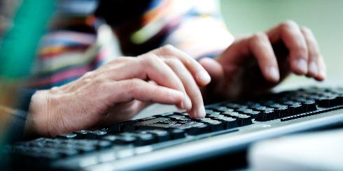 Hænder taster på tastatur